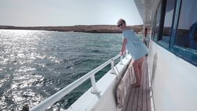 Portrait of a young beautiful sexy Caucasian woman on a yacht in in a blue dress and sunglasses. The concept of vacation. Freedom, sunny summer. Blue ocean on stock video footage
