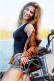 Portrait of young beautiful sexy lady with long hair wearing leather jacket and short shorts sitting on motorcycle. By the river Royalty Free Stock Photos