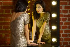Portrait of young beautiful woman standing near mirror with royalty free stock photo