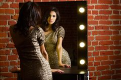 Portrait of young beautiful sexy woman standing near mirror with Royalty Free Stock Image