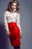 Portrait of young beautiful slender model with long curly hair wearing white silk blouse with red lips print and red skirt royalty free stock photo
