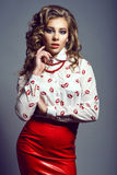 Portrait of young beautiful slender model with long curly hair wearing white silk blouse with red lips print Royalty Free Stock Photography