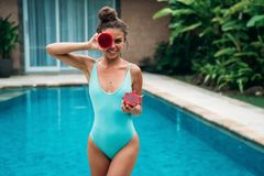 Portrait of young beautiful smileing brunette girl in swimsuit with dragon fruit holding on the breast. Sexy model with. Cute smile posing near swimming pool in Stock Photography