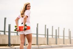 Young Beautiful Blonde Girl Riding Bright Skateboard on the Bridge Royalty Free Stock Photography
