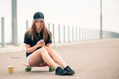 Young Beautiful Smiling Blonde Girl Using Smartphone while Sitting on the Skateboard. Portrait of Young Beautiful Smiling Blonde Girl Using Smartphone while stock photos