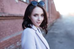 Portrait of young beautiful smiling girl with brown hair in the city. Royalty Free Stock Photo