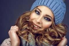 Portrait of young beautiful smiling girl with professional make up and curly hair coming out of her blue knitted hat Royalty Free Stock Photo