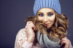 Portrait of young beautiful smiling girl with professional make up and curly hair coming out of her blue knitted hat Stock Photos