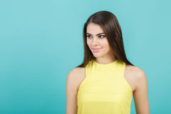 Portrait of young beautiful smiling girl in yellow shirt on blue background. Royalty Free Stock Photography