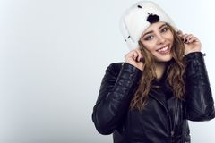 Portrait of young beautiful smiling model wearing trendy black leather unzipped moto jacket and white mink fur hat with black spot royalty free stock image