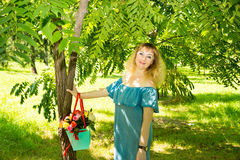 Portrait of the young beautiful smiling woman and flowers outdoors Royalty Free Stock Image