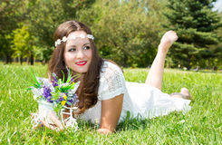 Portrait of the young beautiful smiling woman with long hair and flowers outdoors. Portrait of the young beautiful smiling woman with long hair and flowers royalty free stock photography