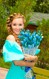 Portrait of the young beautiful smiling woman with long hair and flowers outdoors Royalty Free Stock Photo