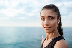 Portrait of young beautiful sportive girl at sunrise over seaside. Portrait of young beautiful brunette sportive girl at sunrise over seaside. Copy space Stock Images