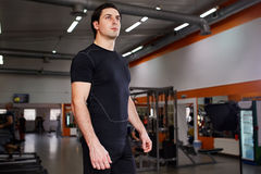Portrait of young beautiful sportsman in the black sportwear while standing with in gym. Horizontal photo. Concentration and motivation. Sportsman in the t Royalty Free Stock Photos