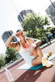 Portrait of a young beautiful sportswoman in the city taking a b Royalty Free Stock Photo