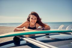 Portrait of beautiful surfer girl at the beach getting ready for stock image