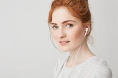 Portrait of young beautiful tender redhead girl with blue eyes in headphones looking at camera smiling over white. Background. Copy space Royalty Free Stock Image