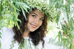 Portrait of a young beautiful in traditional Ukrainian embroidered shirt and a wreath of lilies of the valley Stock Photos