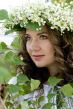 Portrait of a young beautiful in traditional Ukrainian embroidered shirt and a wreath of lilies of the valley Stock Images