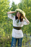 Portrait of a young beautiful in traditional Ukrainian embroidered shirt and a wreath of lilies of the valley Royalty Free Stock Photography