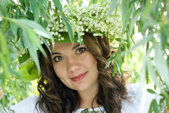 Portrait of a young beautiful in traditional Ukrainian embroidered shirt and a wreath of lilies of the valley Royalty Free Stock Images