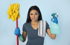 Unhappy and frustrated housekeeping woman holding mop and wash s. Portrait of young beautiful unhappy and frustrated housekeeping woman holding mop and soap Royalty Free Stock Photos