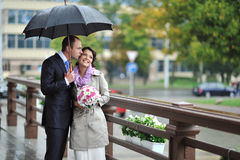 Portrait of young beautiful wedding couple in a rainy day Stock Photos