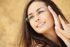 Portrait of young beautiful woman. Close-up portrait of young alluring woman wearing eyeglasses against beige background Royalty Free Stock Image