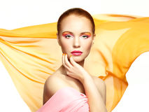 Portrait of young beautiful woman against flying fabric. Beauty Stock Image