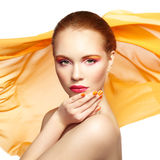 Portrait of young beautiful woman against flying fabric. Beauty Stock Photos