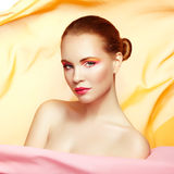 Portrait of young beautiful woman against flying fabric. Beauty Royalty Free Stock Image