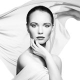 Portrait of young beautiful woman against flying fabric. Beauty Stock Photography