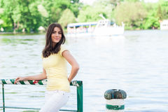 Portrait of young beautiful woman against lake in summer city park. Stock Images
