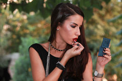 Portrait of a young beautiful woman applying lipstick for lips in the nature Stock Images