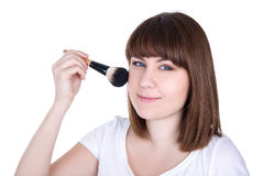 Portrait of young beautiful woman applying make up with brush is Stock Photos