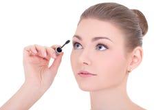 Portrait of young beautiful woman applying mascara on eyelashes. Isolated on white background Royalty Free Stock Photo