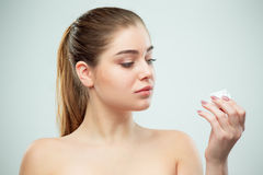 Portrait of young beautiful woman applying moisturizing cream on her face Royalty Free Stock Images
