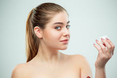 Portrait of young beautiful woman applying moisturizing cream on her face Royalty Free Stock Photography