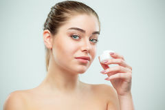 Portrait of young beautiful woman applying moisturizing cream on her face Royalty Free Stock Photo