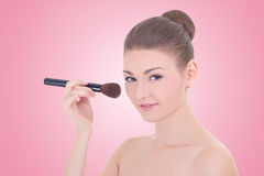 Portrait of young beautiful woman applying rouge or powder with Stock Image
