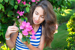 Portrait of young beautiful woman on background of bougainvillea purple violet flowers in blossom Royalty Free Stock Photo