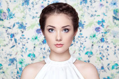 Portrait of young beautiful woman on a background of flowers Stock Photos