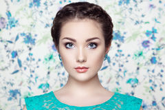 Portrait of young beautiful woman on a background of flowers Royalty Free Stock Images
