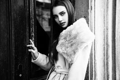Portrait of a young beautiful woman in beige coat, autumn outdoors. Black and white. Young beautiful woman in beige coat standing outdoors. stylish fashion Stock Photos