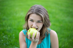 Portrait of young beautiful woman biting apple in summer park Royalty Free Stock Photography