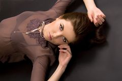 Portrait of a young beautiful woman on black. Beautiful girl lying on black background royalty free stock photo