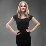 Portrait of a young beautiful woman in black dress. On grey background Stock Photos