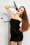Portrait of a young beautiful woman in black dress singing Royalty Free Stock Photos