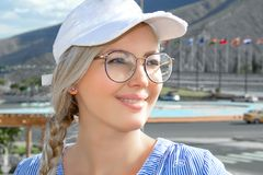 Portrait of a young beautiful woman, blonde in a cap, glasses and with a scythe. On open air. royalty free stock image